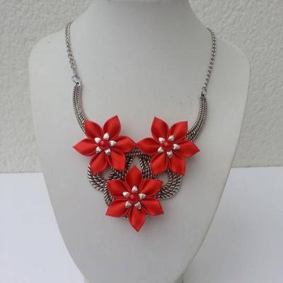 collier plastron en métal argenté avec fleurs de satin rouge